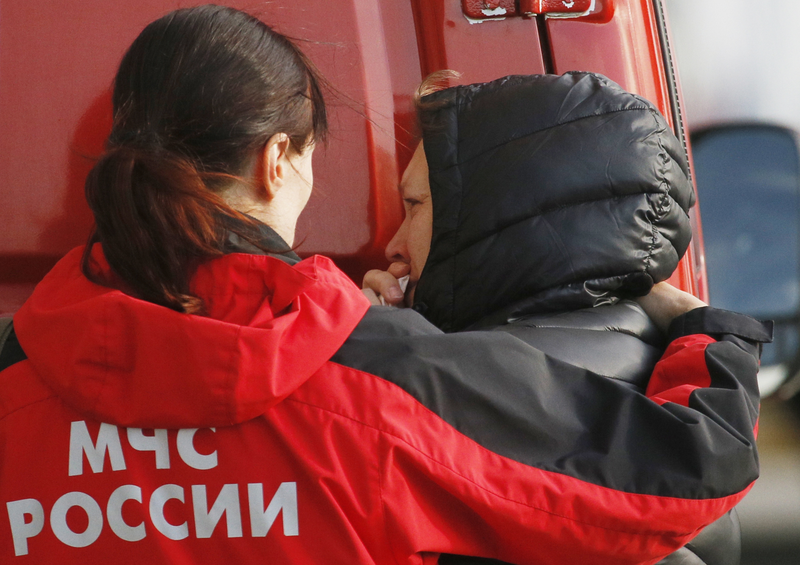 Russian Emergency doctor comforts a relative of a passenger aboard the crashed Russian airliner with 217 passengers and seven crew aboard, as people gather at Pulkovo airport in St.Petersburg, Russia, Saturday, Oct. 31, 2015. Russia's civil air agency is expected to have a news conference shortly to talk about the Russian Metrojet passenger plane that Egyptian authorities say has crashed in Egypt's Sinai peninsula.(AP Photo/Dmitry Lovetsky)